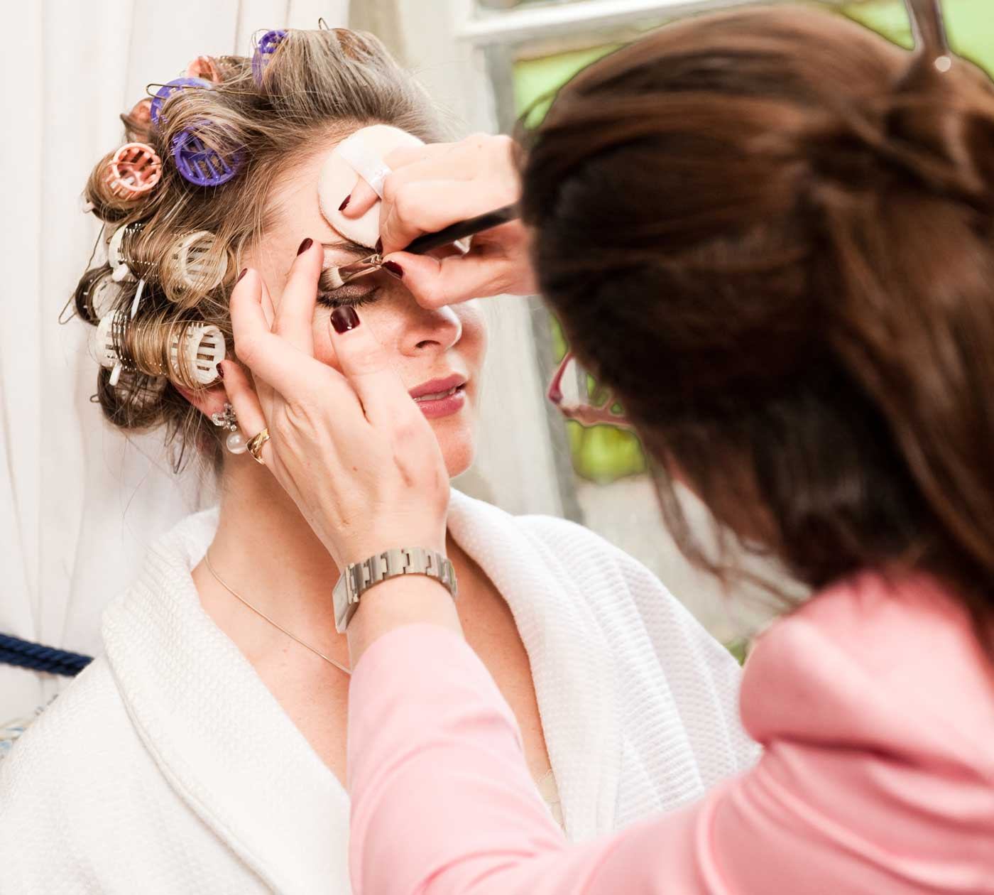Bride hair in rollers makeup artist applying makeup