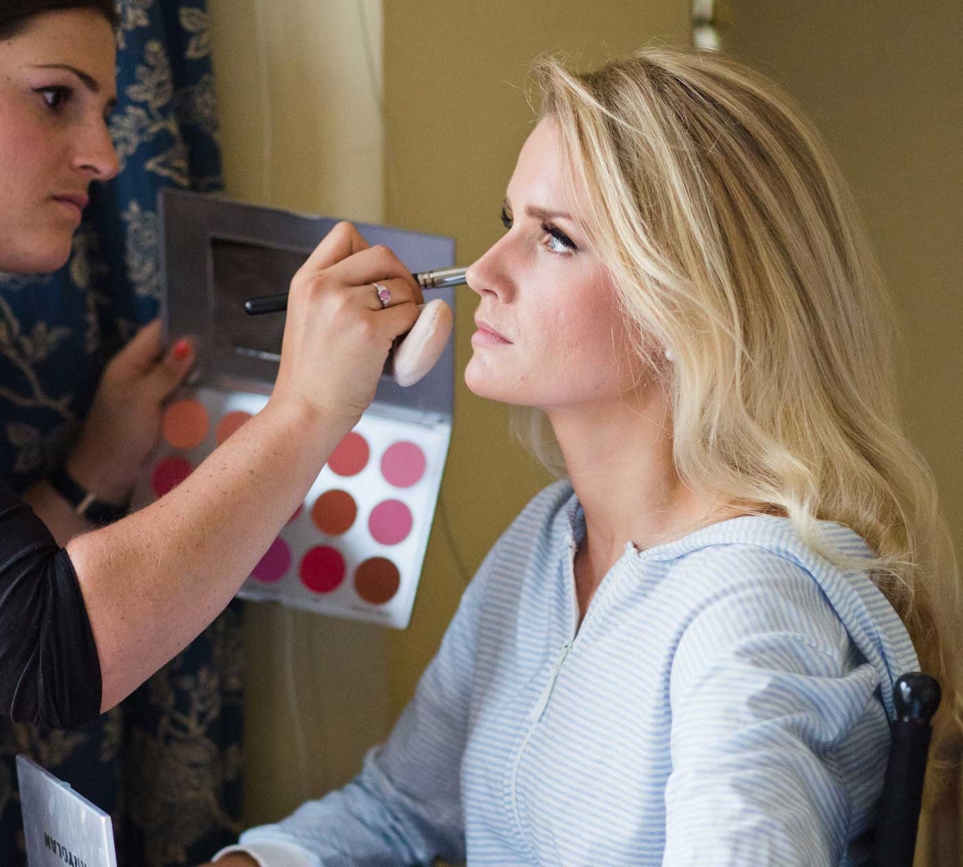 Makeup artist applying makeup to blonde