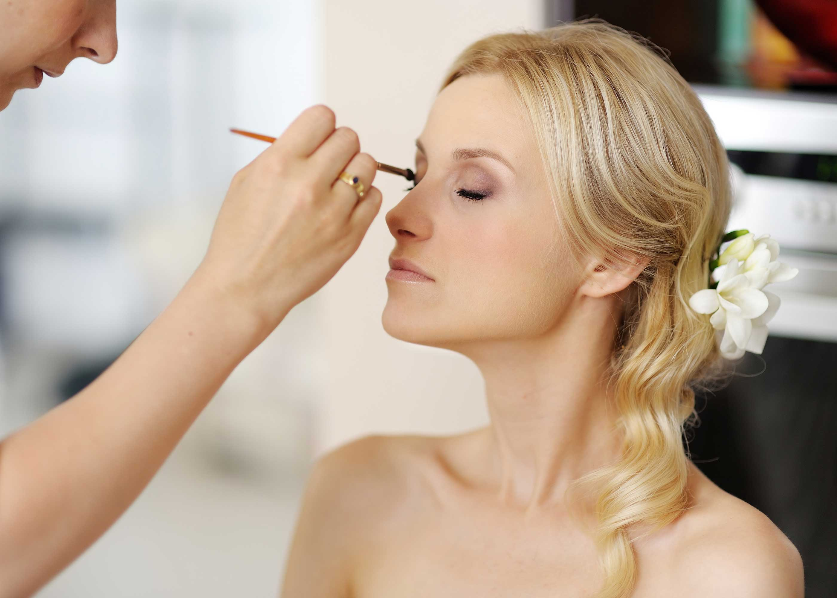 Applying makeup to blonde bride